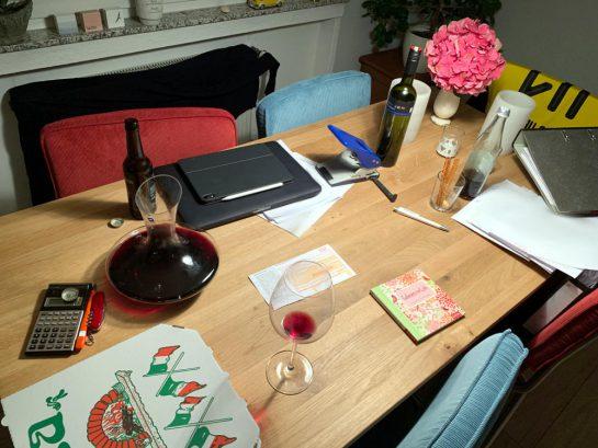 Esstisch mit Laptop, allerlei Papieren, Taschenrechner, einer Pizza, Rotwein, Cola, einer Flasche Bier