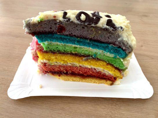 Ein Stück Regenbogenkuchen, dahinter irgendwas Rosanes