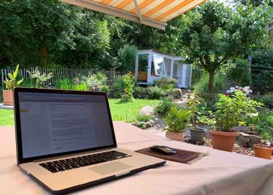 Blick von der Terrasse mit aufgeklapptem Laptop in den Garten.