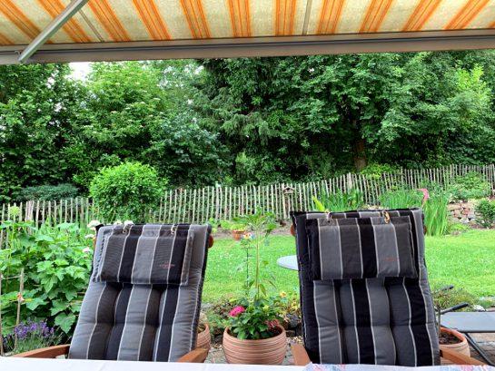 Blick von der Terrasse in den Garten, unter der Markise hindurch. Im Sichtfeld: Zwei Hochlehner-Gartenstühle mit grau gestreiftem Polster.