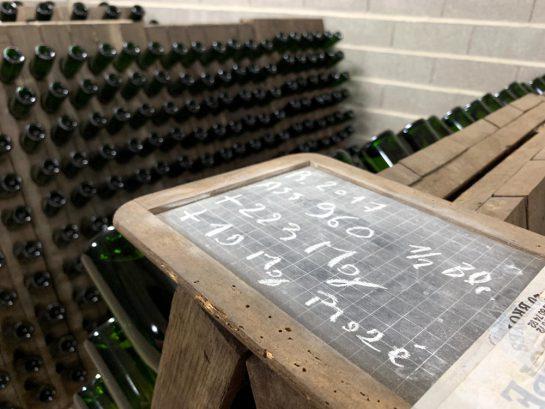 Ein mit Kreide beschriftete Schild, dahinter Ständer mit Flaschen.