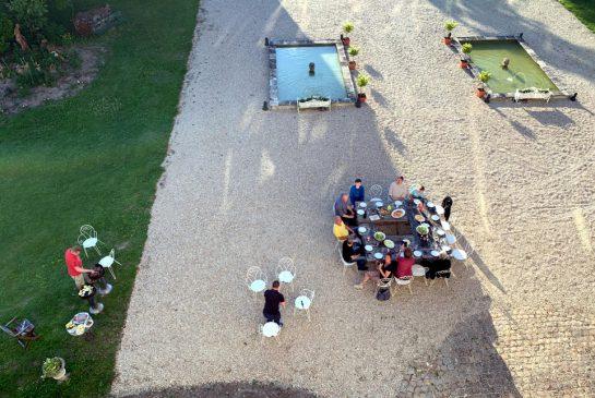 Blick von oben vor das Schloss, wo ein Tisch aufgebaut ist und Leute essen. Dahinter Wasserbecken.