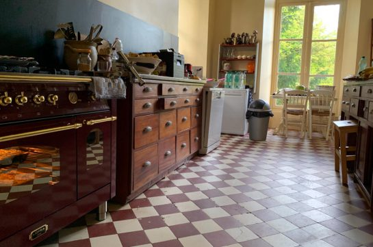 Küche des Schatöchens: Mosaikfliesen, ein altes Buffet, ein Herd mit Backofen, der erleuchtet ist.