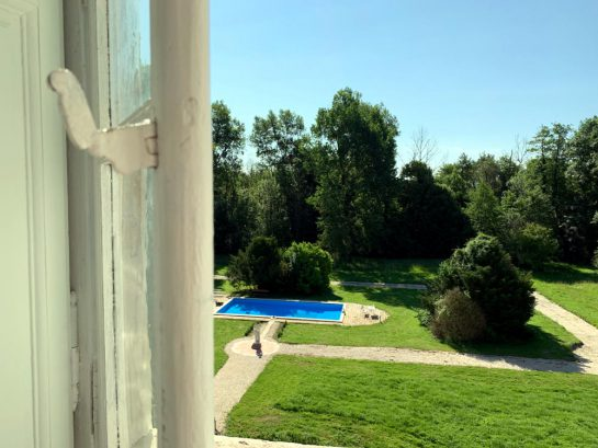 Blick aus einem Zimmerfenster auf Rasen und Wege, darin ein Pool.