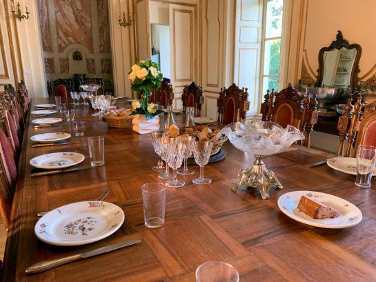 Frühstückstisch mit Tellern, Brotkörben und Pastete. Eine lange Tafel, geschnitzte Stühle.