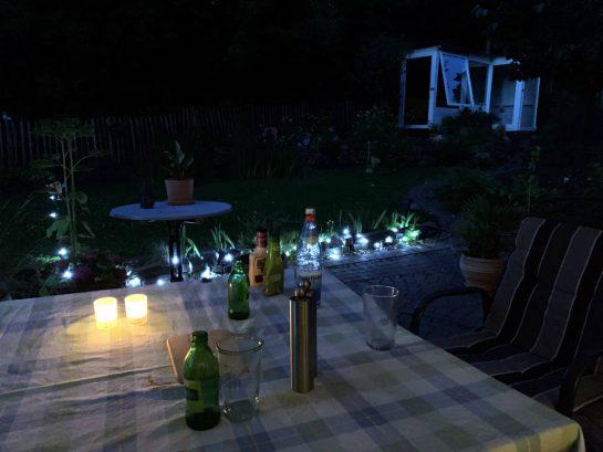 Gartentisch mit Tischdecke, darauf Flachen und Gläser, Beleuchtung. Es ist dämmrig.