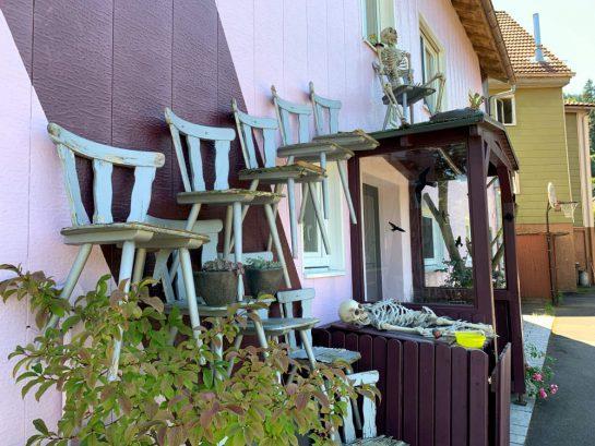 Ein Haus, teils rosa gestrichen. Holzstühle sind an der Fassade angebracht. Sie bilden eine Treppe. Vor der Haustür liegen Plastikskelette.