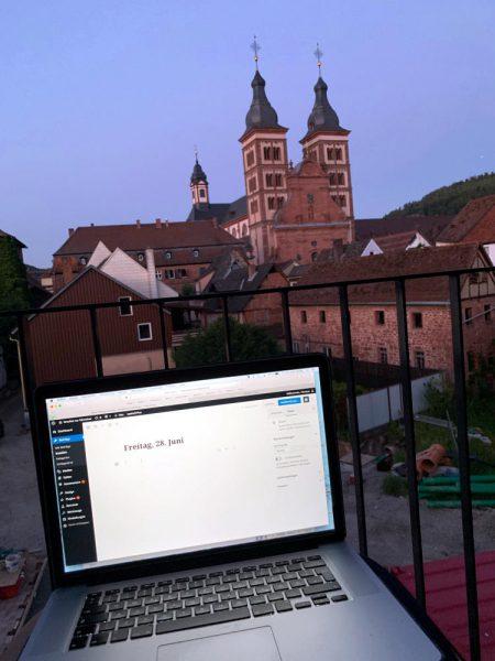 Balkon. Vordergrund: Laptop auf dem Schoss, Backend des Blogs. Im Hintergrund zwei Türme einer Kirche, Altstadt.