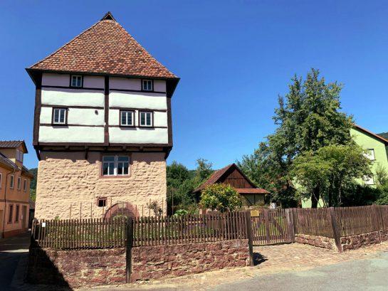 Fachwerkhaus, das auf einem Steinsockel steht. Davor Zaun und ein Nutzgarten.