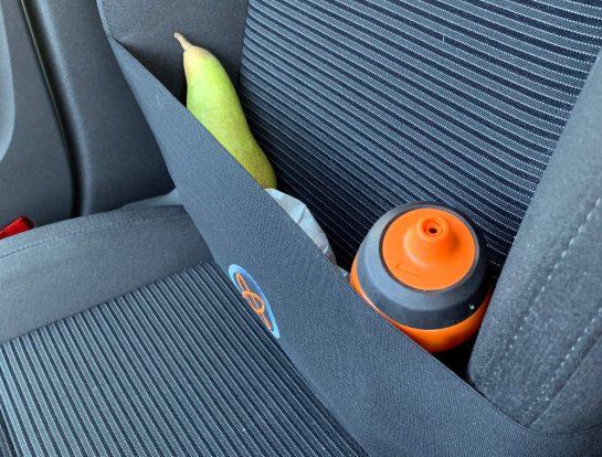 Beifahrersitz mit Gummidings um. Darin stecken eine Birne, eine Brottüte und eine Trinkflasche.