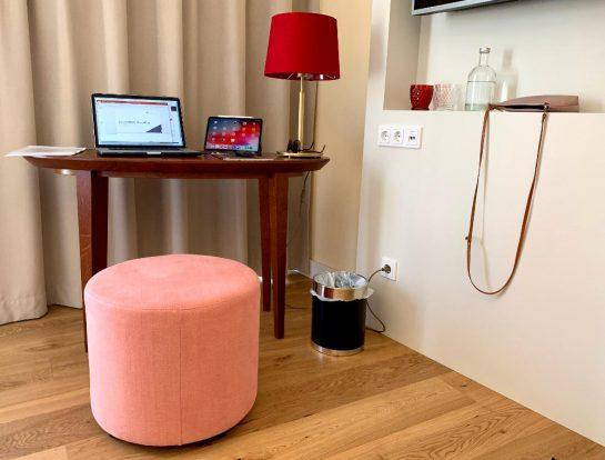 Hotelzimer: Tisch mit MacBook und iPad. Eine Lampe mit rotem Schirm steht daneben. Davor ein rosa Hocker.