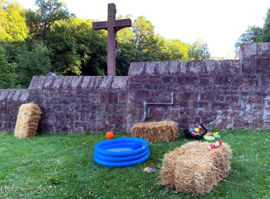 Eine alte Mauer, dahinter ein großes Kreuz. Davor ein Planschbecken und Strohballen.