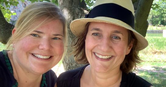 Vanessa (links) und Katja (rechts) mit Strohhut. Beide lächeln. Im Hintergrund Natur.