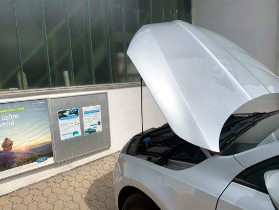 Silbernes Auto mit aufgeklappter Motorhaube