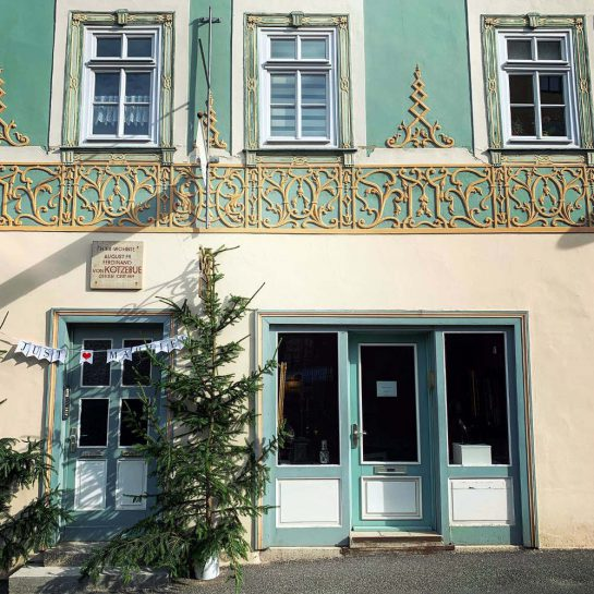 """Goldene Verzierungen an einer türkis-weiß-gelben Fassade. Über der Haustür eine Girlande: """"Just married."""""""