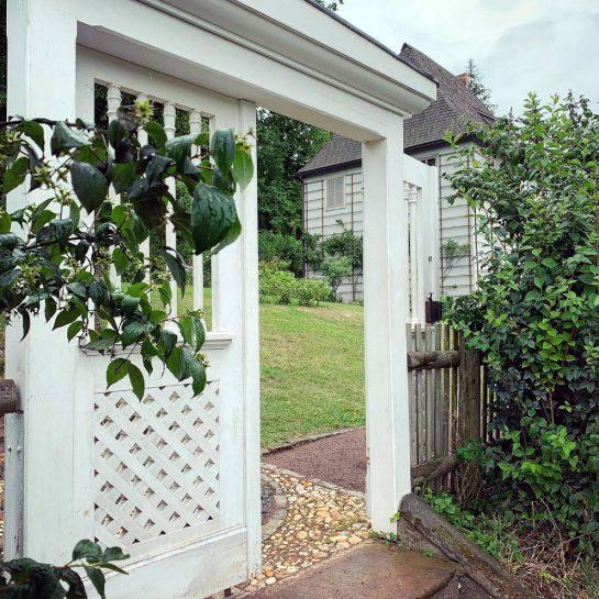 Blick durch ein hohes, weißes Holztor auf ein kleines, graues, weinbranktes Haus