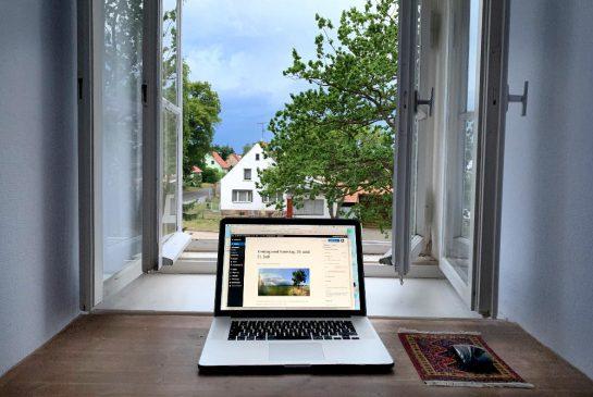 Eine Holzplatte in einer Nische vor einem geöffneten Fenster, darauf ein MacBook, in der Ferne dunkle Wolken.