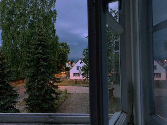Blick auf dem halb geöffneten Fenster. In der Ferne ein weißes Haus gegen dunkelblauen Gewitterhimmel