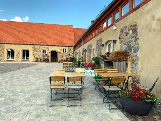 Gutshof Schmerwitz: Renovierter Gutshod, gepflasterter Hof, Biergartenbestuhlung, Blumenkübel