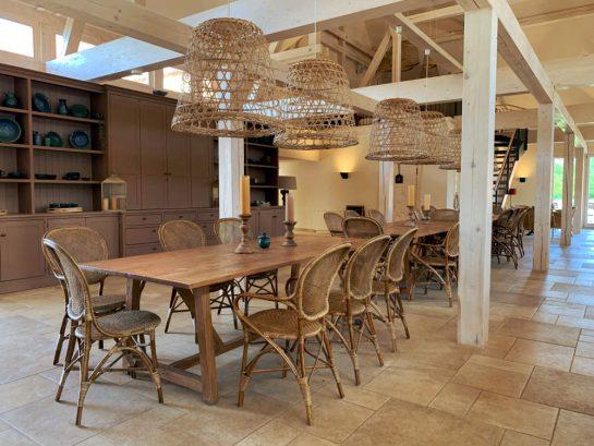 Töpfercafé von innen: hözerne Tische und Stuhle, große Korblampen, weißes Fachwerk