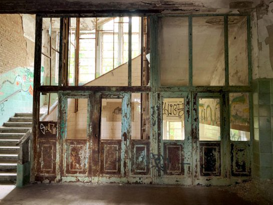 Fahrstuhl im Foyer: grüne Fahrstuhltüren im lichtdurchfluteten Treppenhaus
