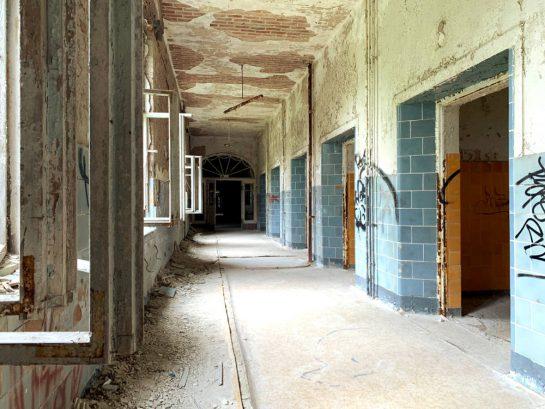 Gang in den Beelitzer Heilstätten: blaue Kacheln bis auf Brusthöhe, danach weiße Farbe. Fenster links, rechts die Zimmer