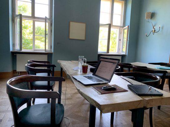 Coworking-Space im Gutshaus: Holztisch, , darauf Laptop und iPad, im Hintergrund große Fenster