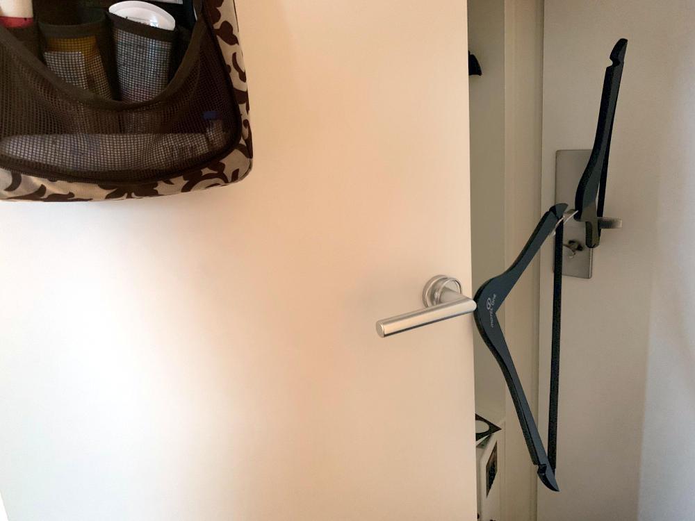 Badezimmertür: An der Türklinge zwei miteinander verhakte Kleiderbügel, die zur Timmertür gehen und die Badtür aufhalten.