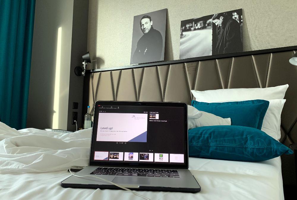 Laptop auf dem Bett, im Hintergrund an der Wand Wotan Wilke Moehring