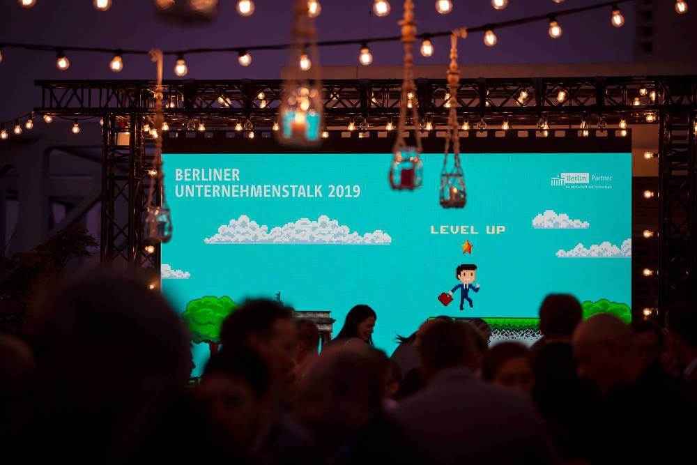 """Leinwand mit einer Grafik im Spiele-Style. Text: """"Berliner Unternehmenswalk 2019"""", """"Level up"""". Es ist dunkel, Lichter brennen."""