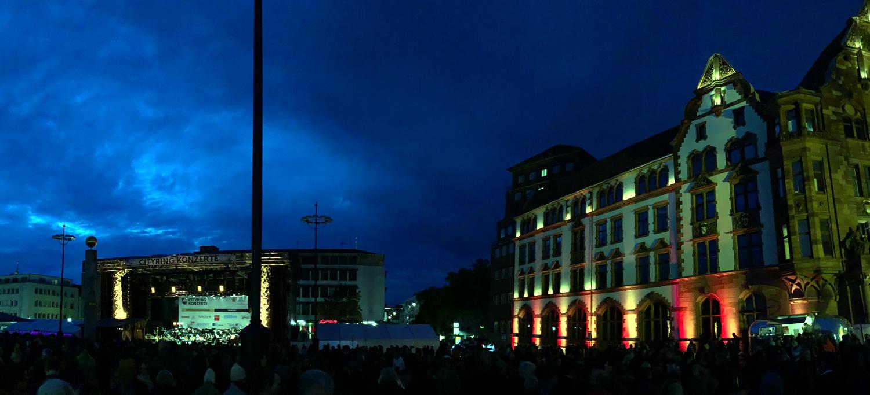 Beleuchteter Friedensplatz in der Abenddäummerung. Rechts das Rathaus in Grün und Rot, voraus die Bühne.