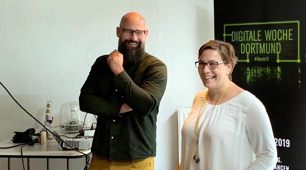 Kai Bünseler und Maike Kranaster vor dem Roll-up der Digitalen Woche. Beide fröhlich lachend.