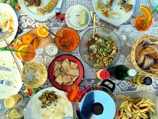 Von oben fotografiert: ein Tisch mit diversen Speisen, weiße Tischdecke, Teller