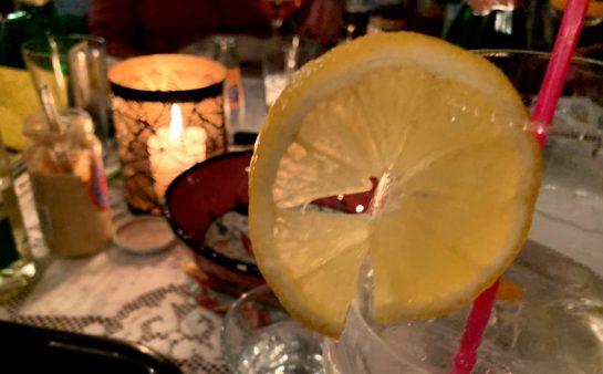 Ein Glas mit einer Zitrone dran, dahinter eine Kerze