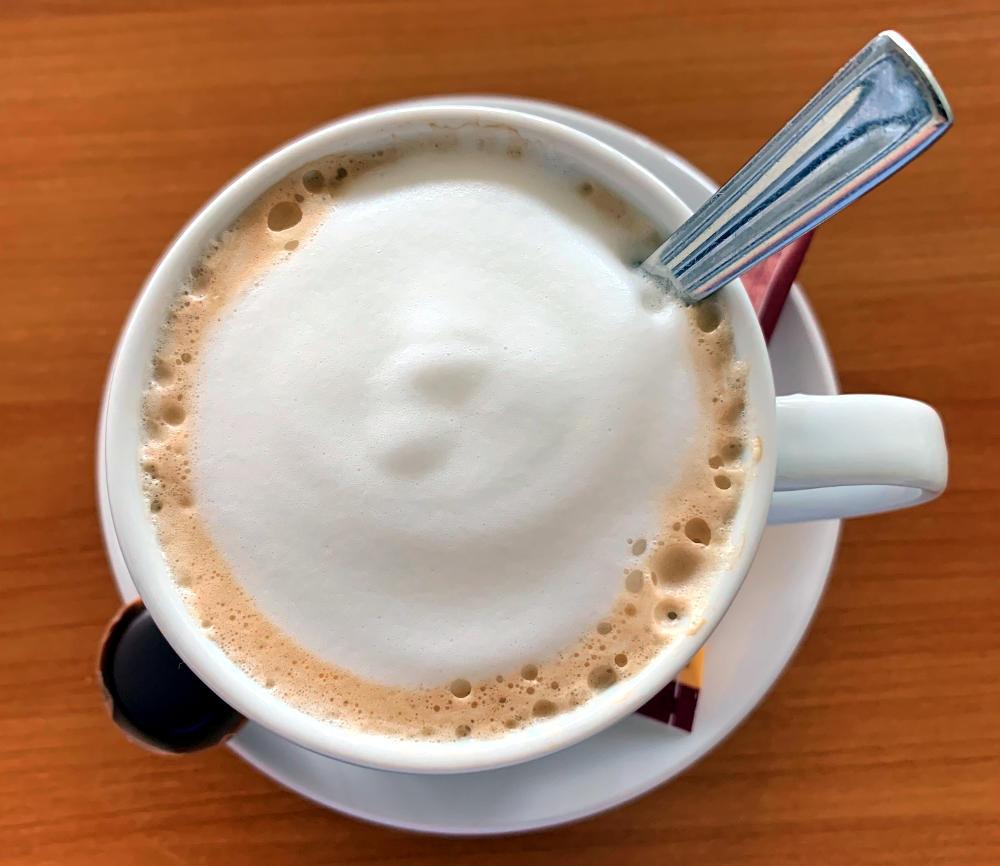 Kaffeetasse von oben mit festem Milchschaum und einem Toffifee