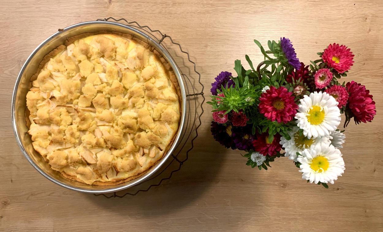 Apfelkuchen in der Sprinfgorm, daneben eine Blumenvase. Von oben fotografiert.
