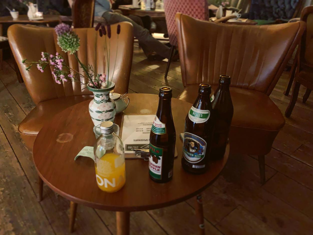 Retrosessel aus Leder, davor ein Tisch mit Bierflaschen und einer Limo