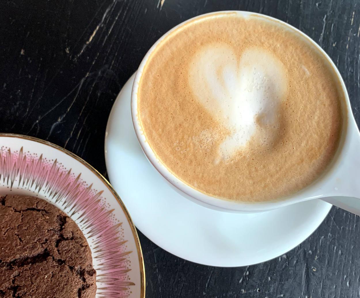 Tasse Milchkaffee mit einem Keks