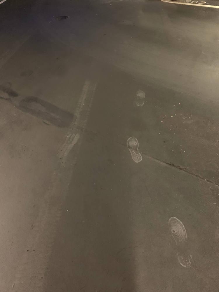 Fußabdrücke auf dem Parkhausboden, die abrupt enden.