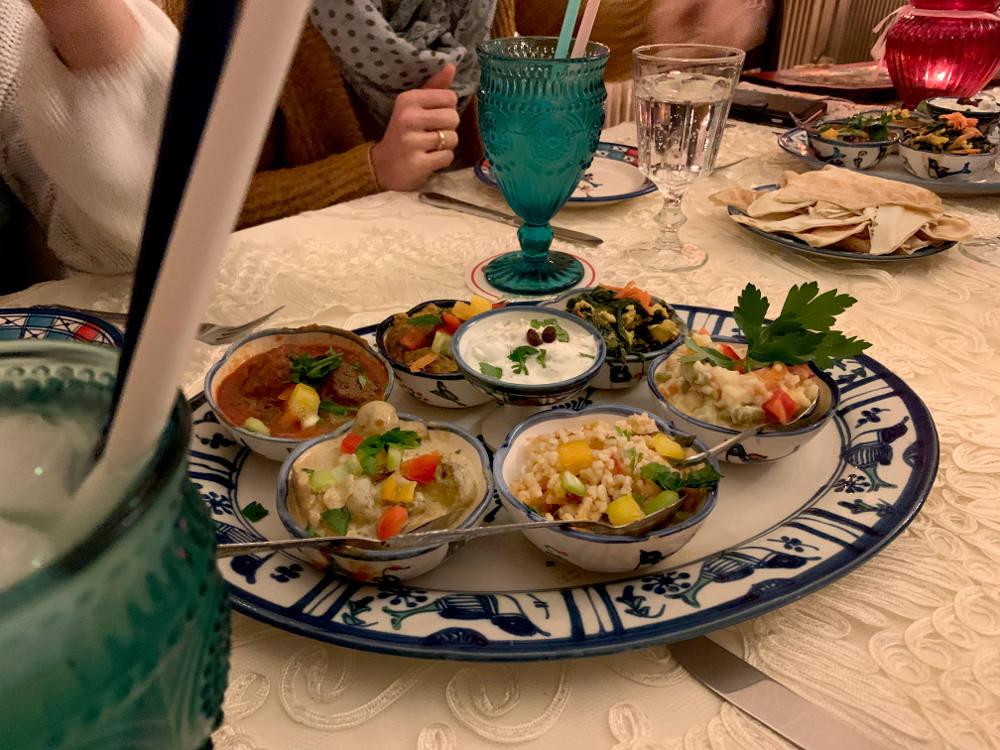 Teller mit kleinen Köstlichkeiten, darunter Humus, Curryhäppchen, Hackbällchen, dazu Brot.