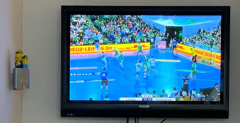 Fernseher mit Handballszene, daneben Minions als Matrjoschka.