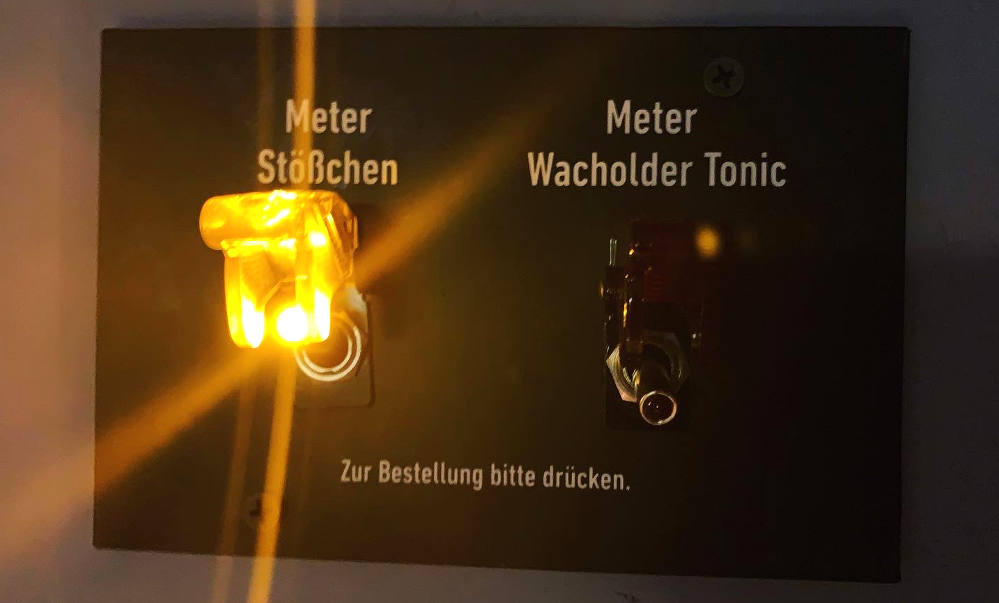 """Zwei Hebel, einer leuchtet. Beschriftung: """"Meter Stößchen"""" und """"Meter Wacholder Tonic""""."""