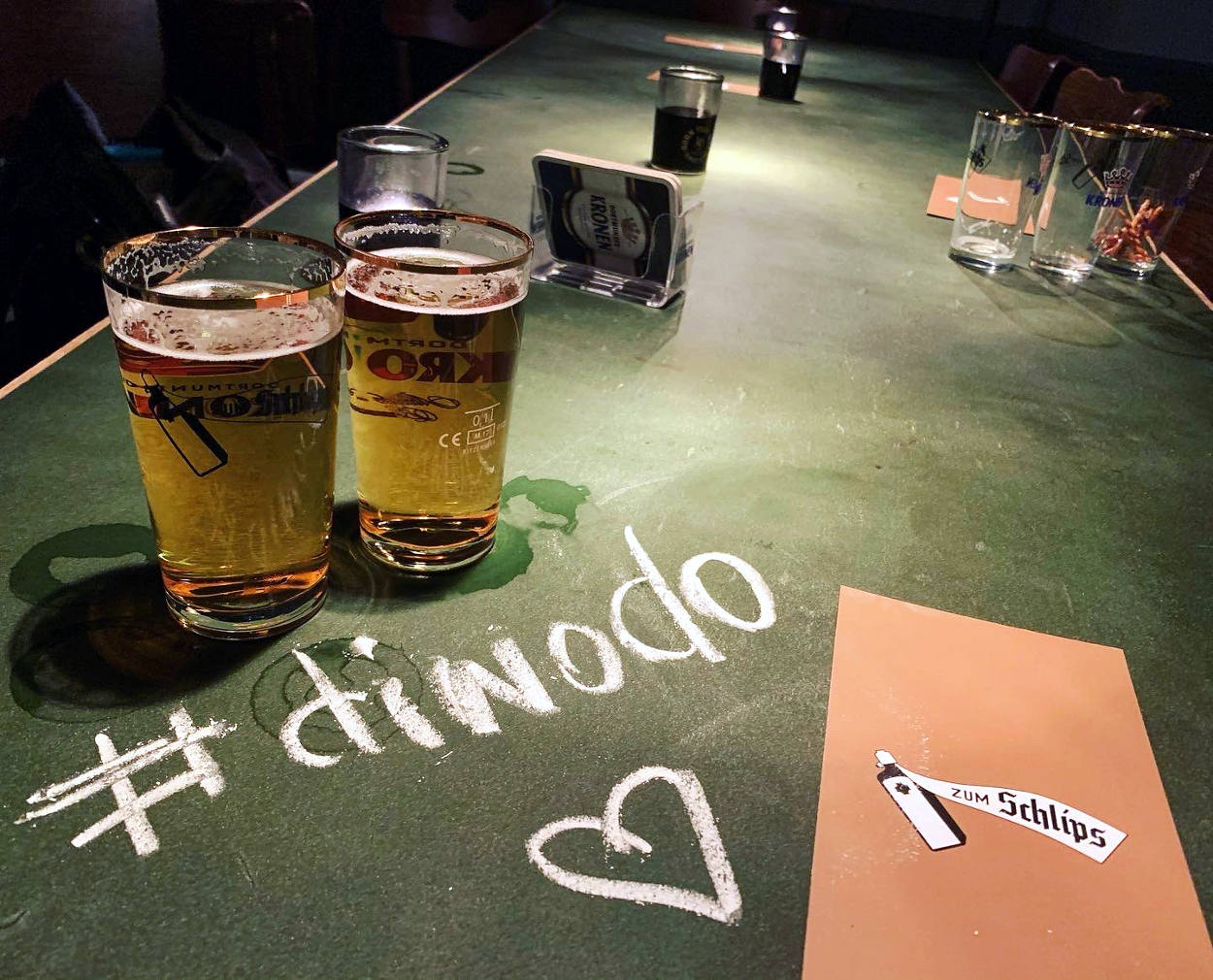 """Zwei Stößchen Bier auf einem grünen Tisch, Beschriftung """"'diwodo""""."""