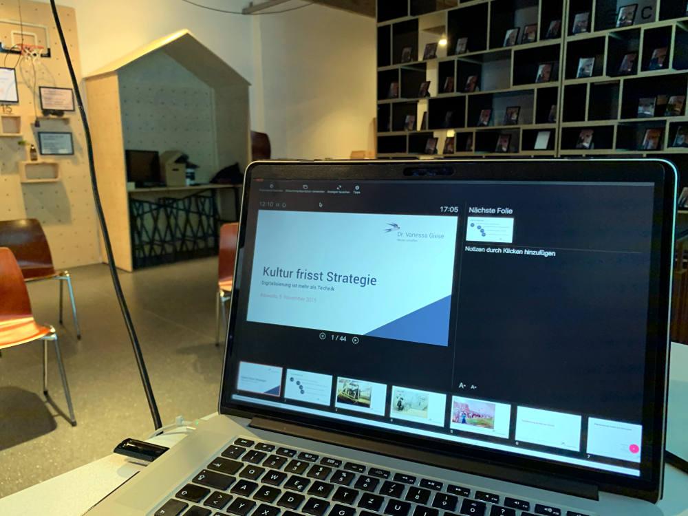 Aufgeklappter Laptop mit Folien in der Referentenansicht, dahinter ein Raum mit Regal und Stühlen