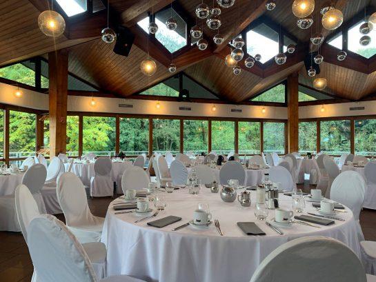 Weiß eingedeckte Tische und Stühle mit Hussen