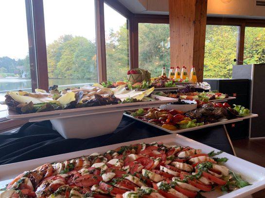 Buffet: im Vordergrund Tomaten mit Mozzarella, dahinter Aufschnitt und Käse. Im Hintergrund ein See.
