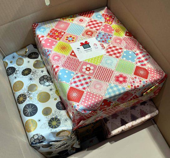 EInzelne, bunt verpackte Schuhkartons in einem großen Umkarton