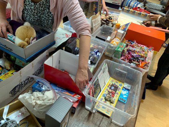 Hände, die in Sachspenden greifen: Süßigkeiten, Stofftiere, Aufkleber