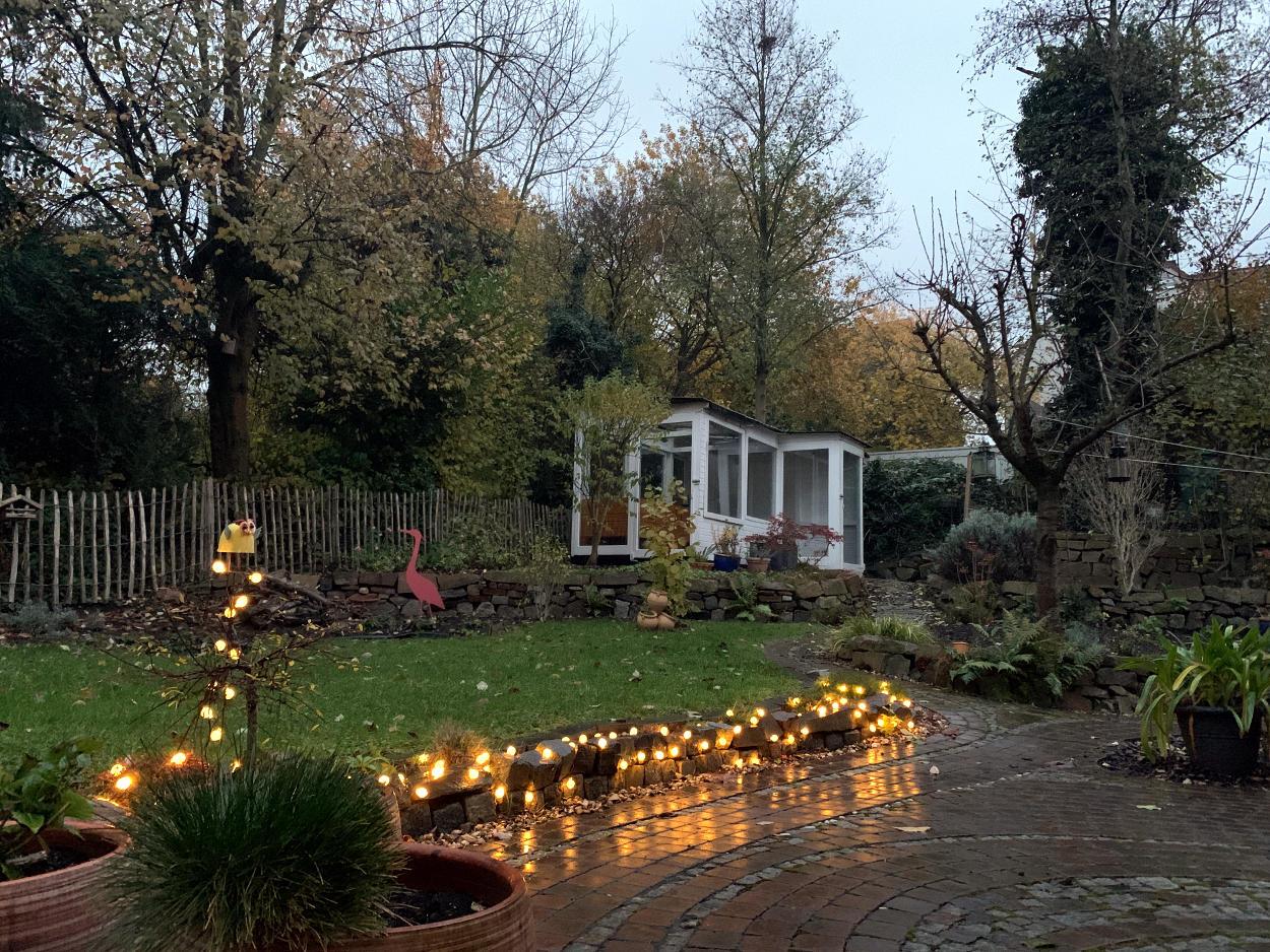 Lichterkette, die Terrassenumgrenzung entlang, dahinter verregneter Herbstgarten im Dämmerlicht.