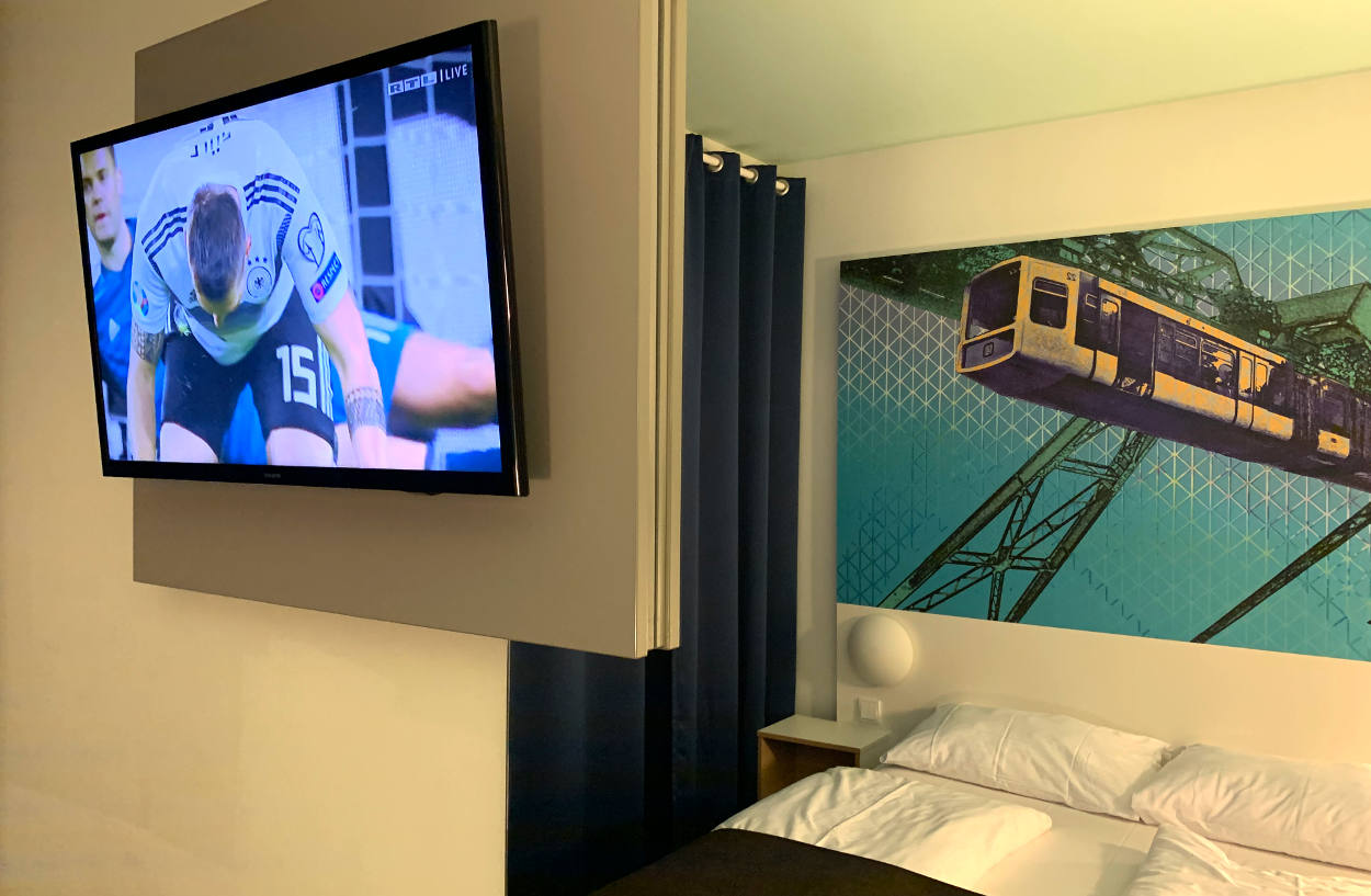 Im Spiegel: Bett, darüber ein Bild von der Schwebebahn. Daneben ein Fernseher mit deutschem Nationalspieler.